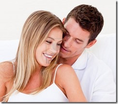 6571060-young-man-kissing-his-wife-sitting-on-bed-at-home